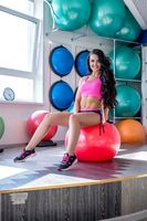 Smiling girl posing while sitting on fitness ball