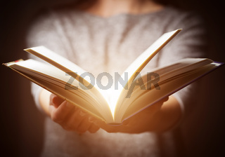 Light coming from book in woman#39;s hands in gesture of giving