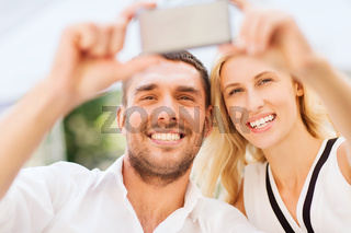 happy couple taking selfie with smartphone
