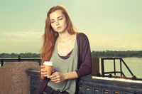 Portrait of beautiful brown haired teen girl standing and looking down. She keeping takeaway drink. Urban city scene. Outdoors portrait vintage film color imitation.