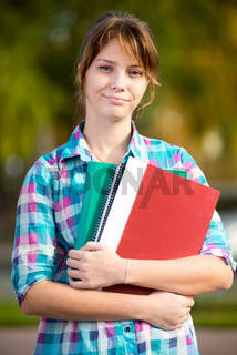 Portrait of young alluring woman holding education books. Student girl.