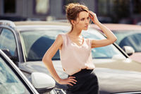 Young fashion business woman beside her car