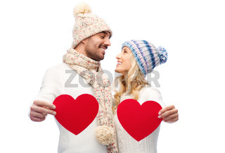 smiling couple in winter clothes with red hearts