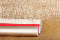 Rolls of multicolored wrapping paper for gifts on gold background.
