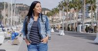 Casual woman enjoying a walk through a marina
