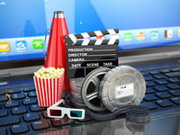 Video or movie online internet concept. Film reels, clapperboard and pop corn on laptop keyboard.