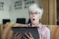 One Senior Woman looks in amazement at the screen