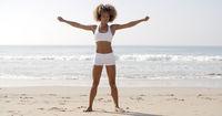 Woman Practices Yoga On A Beach