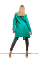 fashion woman in vivid color green coat rear view
