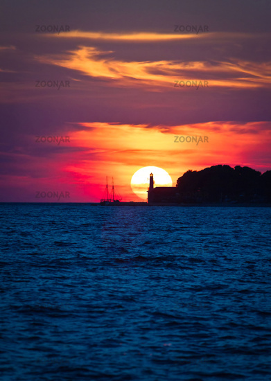 Sailboat and lighthouse on dramatic sunset