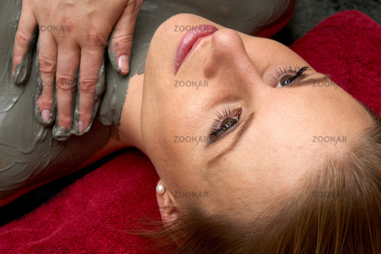 Young woman receiving a treatment with clay residue