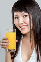 asian woman drinking orange juice