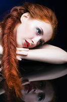 Young woman with ginger hair over reflection mirror on blue background