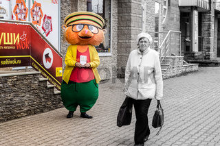 The Hamster costumed actor is happy whilst the old woman is sad. Is the old woman acting or is the hamster really as sad as well? This image was captured in Ufa