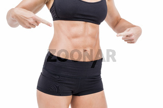 Female athlete pointing her abs