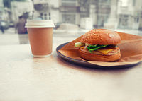 Burger and takeaway coffe  on table in pub selective focus, toned image.