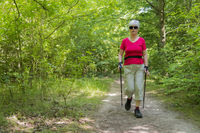 An elderly lady in sports nordic walking on a forest path.