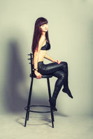 Full length portrait of young brunette woman posing against gray background sitting on bar stool