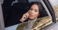 Serious female executive on phone in limousine