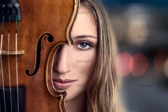 Pretty Young Woman Peeking Behind Violin
