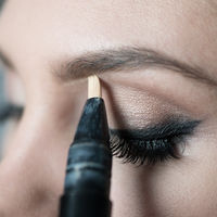 Close Up of Woman Applying Make Up Along Brow Line