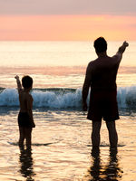Father and son in front of evening sky seaside