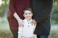 Young Mixed Race Boy Portrait Outdoors With Parents Behind