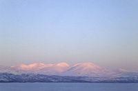 Mountain range in evening light at lake Tornetraesk