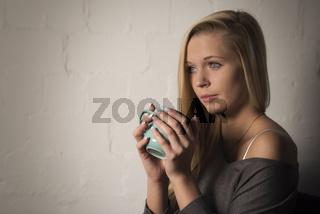 blondes mädchen an einer wand hält einen kaffeebecher