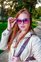 Close up fashion portrait of pretty seductive young woman with funny violet sunglasses, posing outdoor. Red lips, long hairstyle.