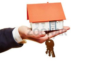 Hand hält ein Haus mit Schlüsseln