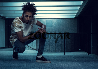 Curly-Haired Young Guy Squatting Inside a Building