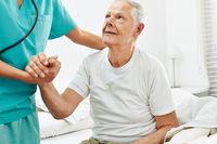 Altenpfleger hilft Senioren beim Aufstehen