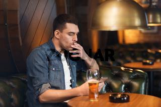 man drinking beer and smoking cigarette at bar