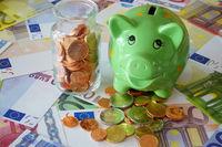 Sparschwein und Glas mit Euromünzen auf Geldscheinen