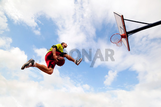 Young man jumping and making a fantastic slam dunk playing streetball