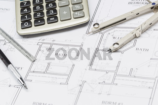 Pencil, Ruler, Compass and Calculator Resting on House Plans