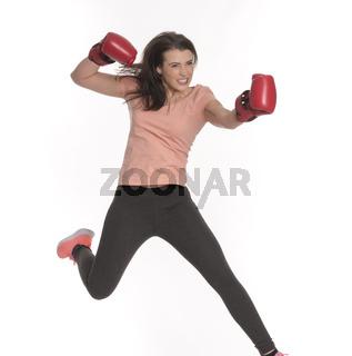 junge frau mit boxhandschuhen macht einen sprung nach vorne