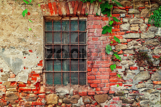 Fragment of old abandoned brick house with closed window behind iron bars in small italian town in Piedmont