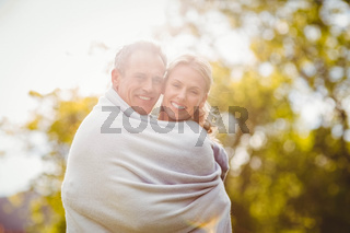 Cute couple hugging with a blanket around