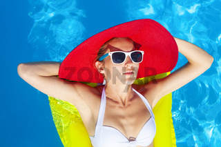 Woman with perfect tanned body lying on yellow air mattress in the pool