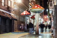 People walking on the street filled with giant mushrooms. Spain