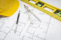 Hard Hat, Pencil, Level and Compass Resting on House Plans