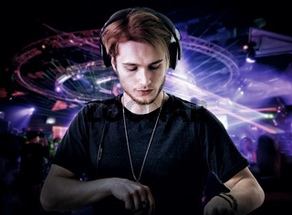 Close-up of young dj playing music in club
