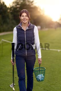Golferin mit Ballkorb auf der Driving Range
