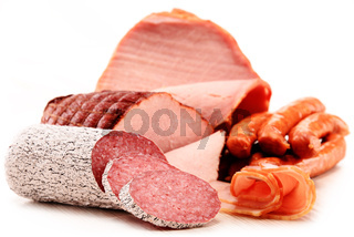 Assorted meat products including ham and sausages isolated on white