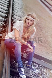 Junge Frau im Hippie-Look mit alter Kamera, sitzt auf Schienen