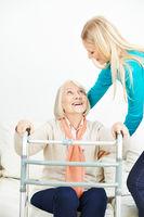 Pflegehilfe hilft Seniorin beim Aufstehen
