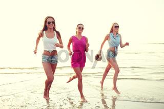 group of smiling women running on beach