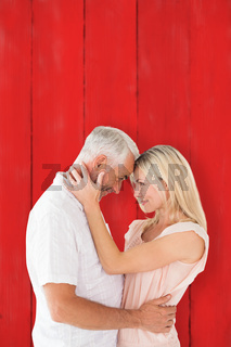 Composite image of affectionate couple standing and hugging